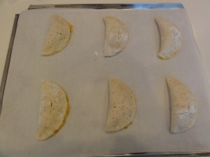 10. Fold over the cheese mixture to make half-moon shapes, with the cross on top. Pinch edges together with moistened fingers, crimp with a fork.